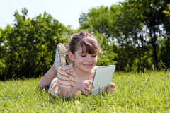 Little girl lying and play with tablet pc Royalty Free Stock Photo