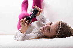 Little girl lying playing with a game controller royalty free stock photos