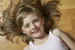 Little girl lying and restingon a wooden floor Stock Photography