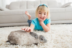 Little girl lying on rug stroking the rabbit. At home in the living room Stock Image