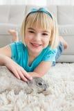 Little girl lying on rug stroking the rabbit Stock Photos