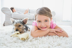 Little girl lying on rug with yorkshire terrier smiling at camera Royalty Free Stock Images