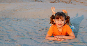 Little girl lying on sand Royalty Free Stock Images