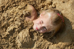 Little girl lying on sand Stock Photo