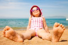 Little girl lying on a sandy beach Stock Photos
