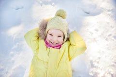 Little girl lying on snow Stock Images