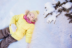Little girl lying on snow. Royalty Free Stock Photos