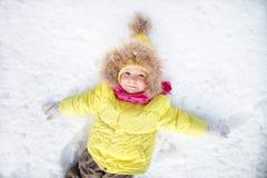 Little girl lying on snow Royalty Free Stock Photos