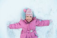 Little girl lying on snow Royalty Free Stock Photo