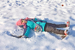 Little girl lying on a snow Royalty Free Stock Image