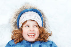 Little girl lying on a snow. Royalty Free Stock Images