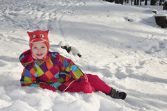 Little girl lying in the snow in the pine forest. Stock Photography