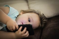 Baby girl playing with mobile phone royalty free stock image