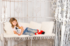 Little girl lying on sofa at home. Kid playing having fun on couch. Stock Image