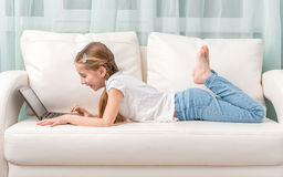 Little girl lying on sofa looks at notebook and laughs Royalty Free Stock Photo