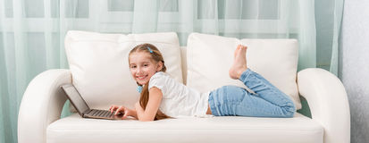 Little girl lying on sofa looks at notebook and laughs. Cute little girl lying on white sofa looks at notebook and laughs Royalty Free Stock Photo