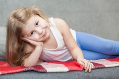Little girl lying on the sofa Stock Photos
