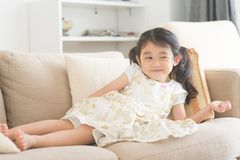 Little girl watching tv. Little girl lying on sofa and watching tv. Asian family at home, living lifestyle indoors Royalty Free Stock Image