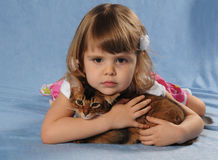 Little girl lying with somali kitten ruddy color. Very sad and upset and thinking of something stock photography