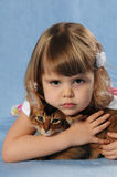 Little girl lying with somali kitten ruddy color. Very sad and upset and thinking of something Stock Images