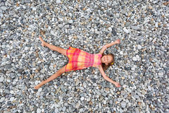 Little girl lying on stones on stone seacoast Stock Photo