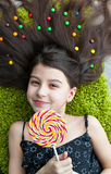 Little girl lying among sweets and candy with lolipop Royalty Free Stock Photography