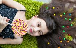 Little girl lying among sweets and candy with lolipop Stock Image