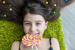 Little girl lying among sweets and candy with lolipop Royalty Free Stock Photos