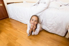 Little girl lying under bed at home and looking at camera Royalty Free Stock Images
