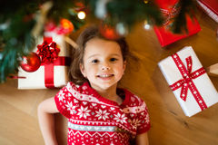 Little girl lying under Christmas tree among presents, Royalty Free Stock Photos