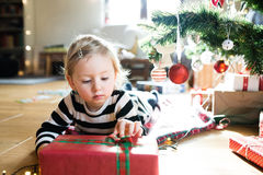 Little girl lying under Christmas tree among presents Royalty Free Stock Images