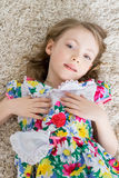 Little girl is lying on the white carpet Stock Photography
