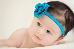 Baby who smiles. Little girl lying on a white cover with blue flower color Stock Photography