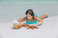 little girl lying on white sand beach of Atlantic ocean Royalty Free Stock Image