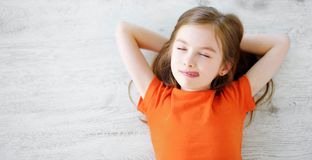 Little girl lying on white wooden floor Royalty Free Stock Images