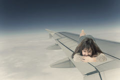 Little girl lying on the wing of an aircraft facing the camera Royalty Free Stock Images