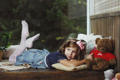 The little girl lying on a wooden box. Royalty Free Stock Photo