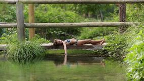 Little girl lying on a wooden walkway touching the water stock video footage