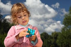 Little girl with magic cube outdoor Stock Image