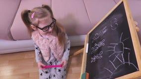 Little girl with magic wand near blackboard. In room stock footage