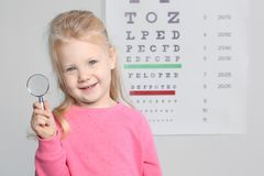 Little girl with magnifier visiting children`s doctor stock image