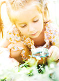 Little girl with magnifying glass looks at flower Royalty Free Stock Photos