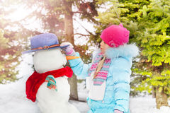 Little girl with make snowball in the winter park Stock Photos