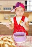 Little girl make sweet rolls Stock Photos