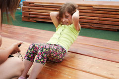 Little girl makes abdominal crunches stock photography