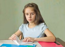 Little girl makes crafts from paper stock photo