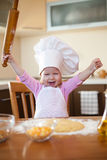 Little girl makes dough on kitchen Royalty Free Stock Photo
