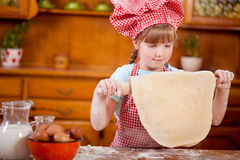 Little girl makes dough on kitchen with rolling pin Royalty Free Stock Photography