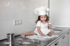 Little girl makes dough on kitchen with rolling pin.  Stock Photo