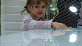 Little girl makes faces in front of a mirror stock footage